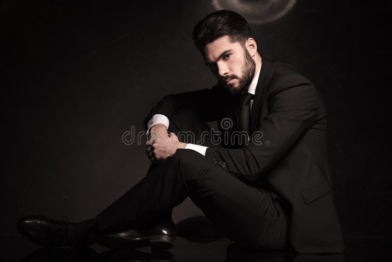 Homme dramatique d'affaires s'asseyant sur le plancher photographie stock