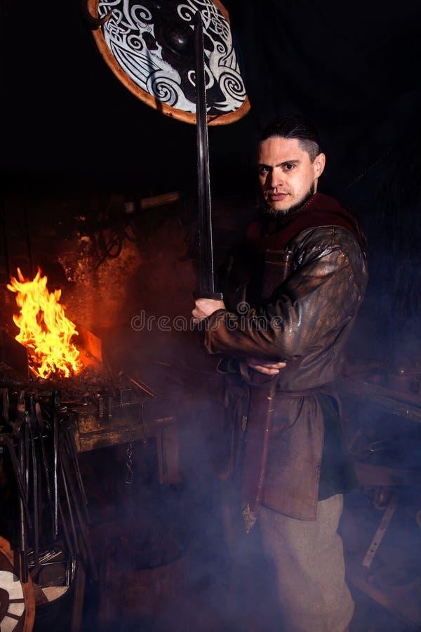 Homme du foyer un du feu de peau de bouclier de hache d'équipement d'arme de guerrier de forgeron de forge de reconstitution de s photographie stock libre de droits