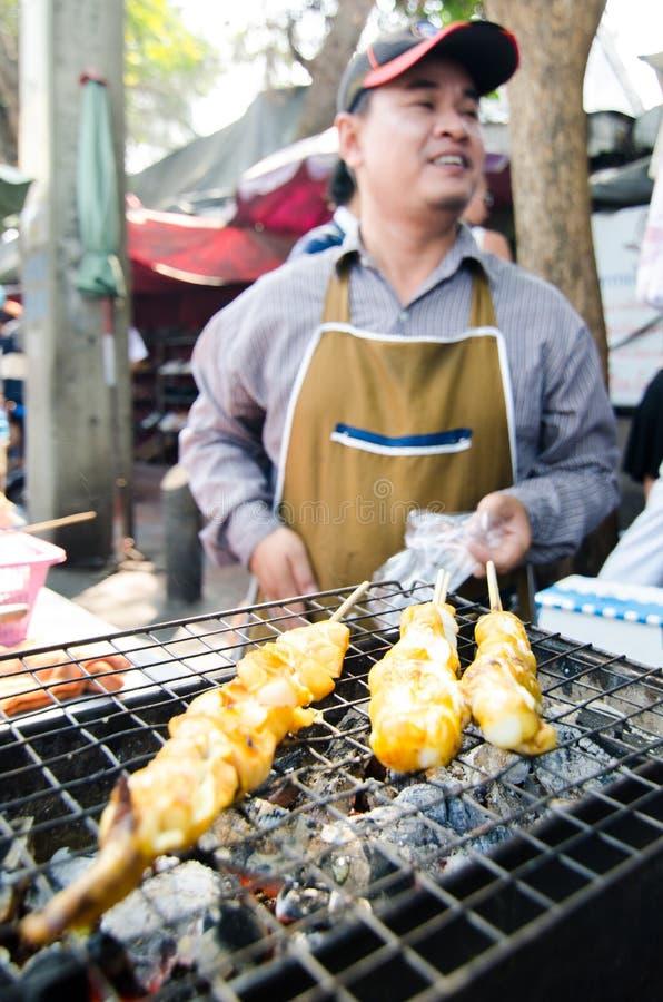 Homme du marché vendant le calmar grillé. image libre de droits