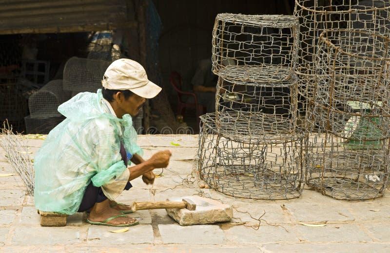 Homme effectuant des paniers de pêche photo stock