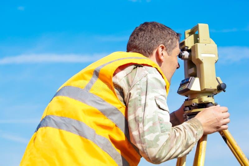 Homme effectuant la mesure avec le théodolite image libre de droits