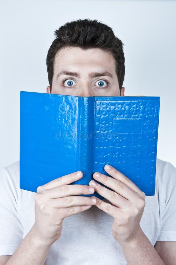 Homme effrayé affichant un livre photos stock