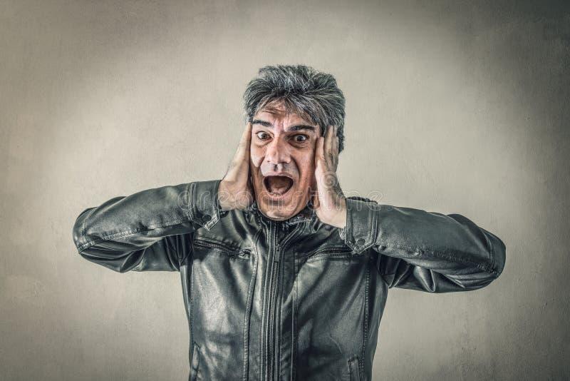 Homme effrayé avec des mains sur le visage images stock
