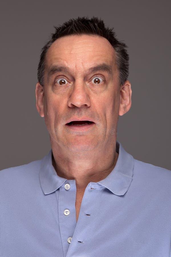 Homme effrayé choqué sur le fond gris images stock