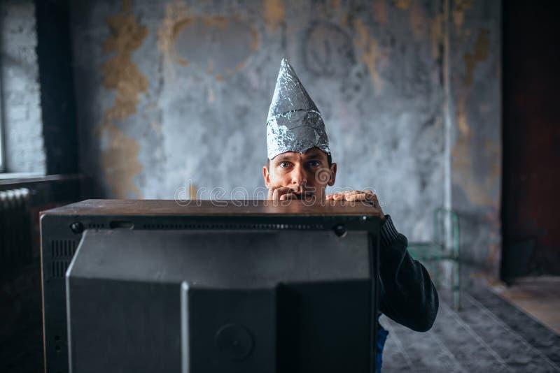 Homme effrayé dans la montre TV, UFO de chapeau de papier d'aluminium images libres de droits