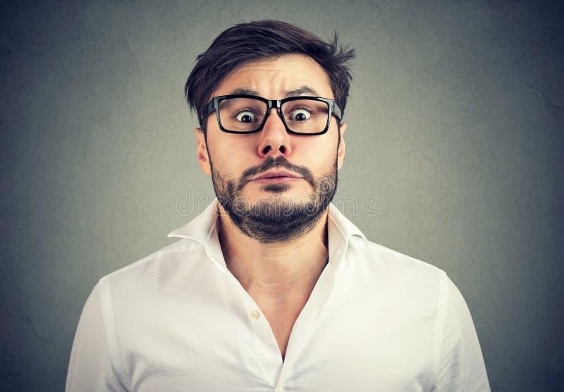 Homme effrayé regardant impatiemment l'appareil-photo image libre de droits