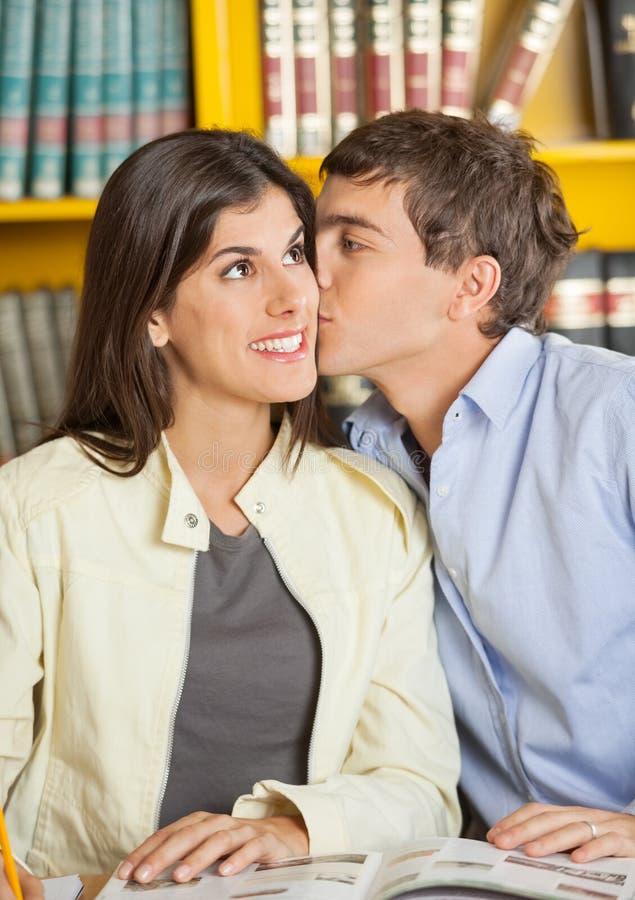 Homme embrassant l'amie à la bibliothèque universitaire photographie stock