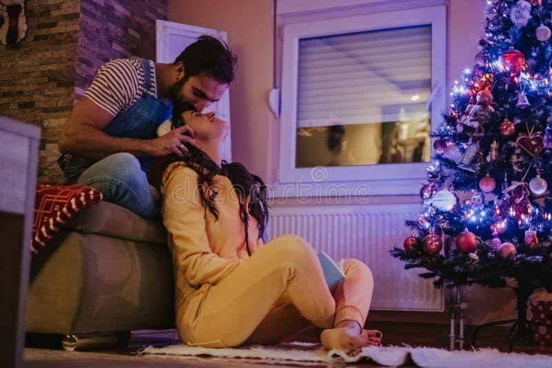 Homme embrassant l'amie devant l'arbre de Noël photographie stock