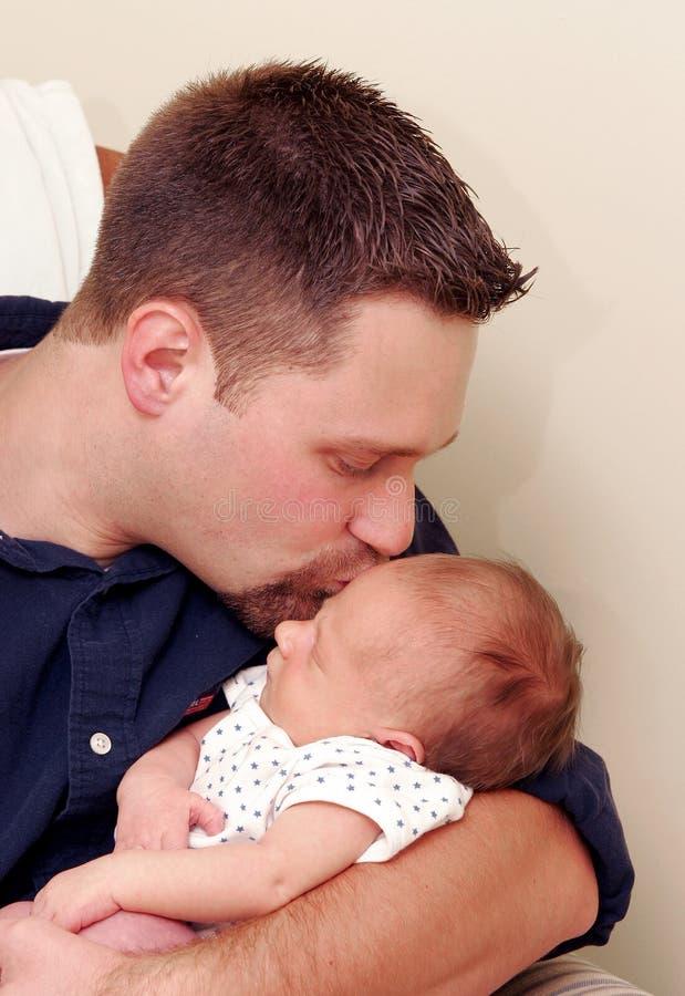 Homme embrassant la chéri nouveau-née image stock