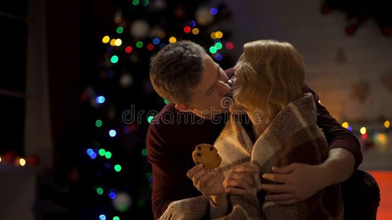 Homme embrassant la dame aimante et la couvrant de plaid, nuit de Noël romantique photos stock