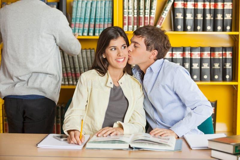 Homme embrassant la femme à la bibliothèque universitaire photographie stock