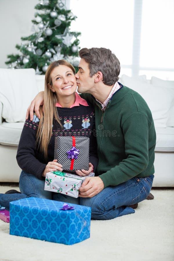 Homme embrassant la femme sur la joue avec des cadeaux de Noël photographie stock libre de droits