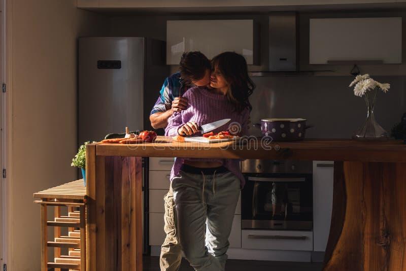 Homme embrassant le cou de son amie tout en faisant la salade photographie stock libre de droits