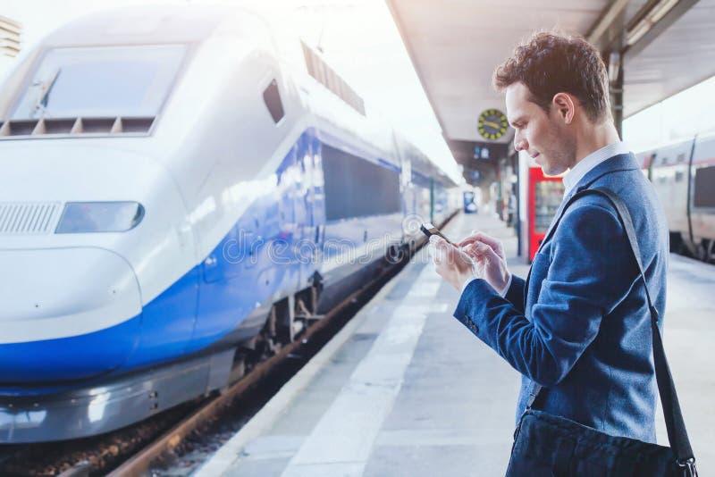 Homme employant l'application mobile sur son smartphone à la station de train photo stock