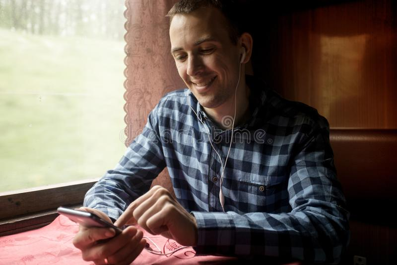 Homme employant l'application mobile sur son smartphone ? la station de train, voyage d'affaires photographie stock