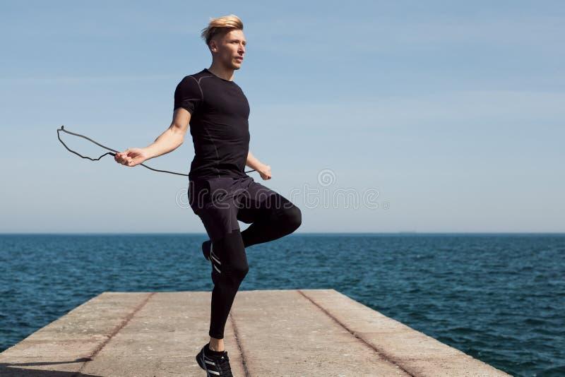 Homme employant la corde à sauter se tenant sur le pilier photo stock