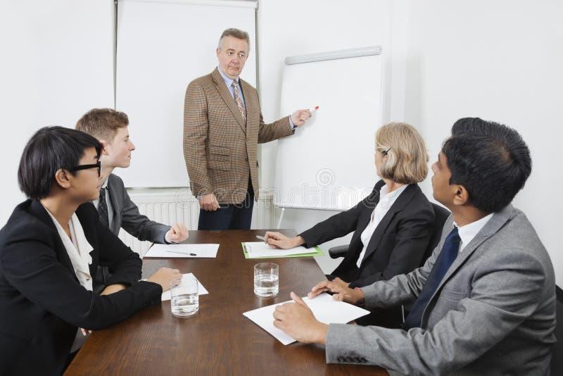 Homme employant le tableau blanc lors de la réunion d'affaires photo stock