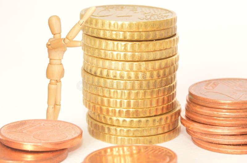 Homme en bois empilant des pièces de monnaie image libre de droits