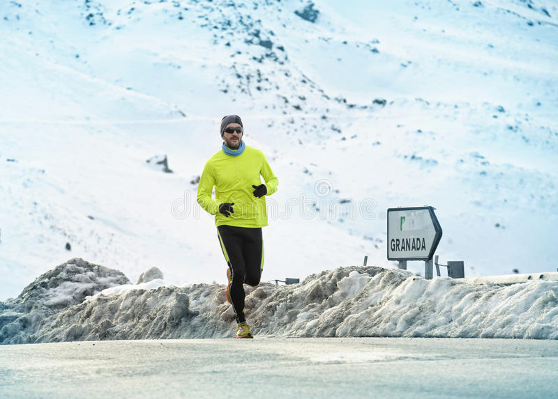 Homme en bonne santé de sport courant sur la route goudronnée aux montagnes de neige dans la séance d'entraînement dure de coureu photo libre de droits