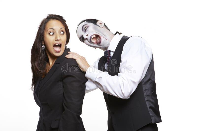 Homme en cou mordant de filles de costume costumé de Dracula photo libre de droits
