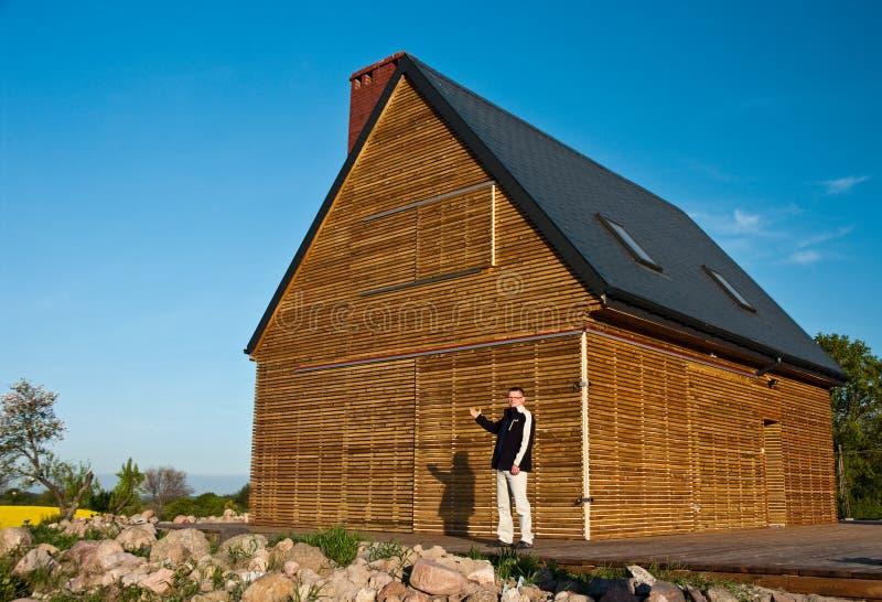 Homme en dehors de maison en bois photo stock