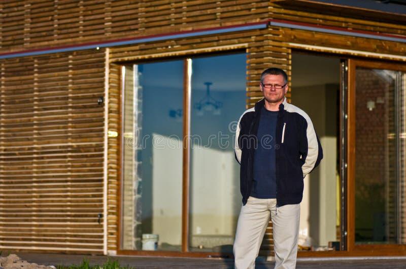 Homme en dehors de nouvelle maison d'eco photographie stock