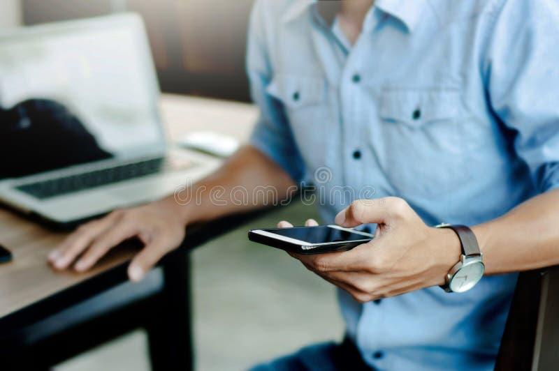 Homme en forme occasionnelle utilisant le téléphone portable au bureau moderne image stock
