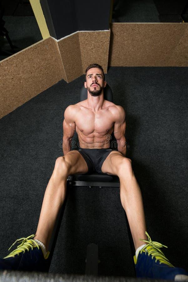 Homme en gymnastique sur l'exercice de machine photo libre de droits