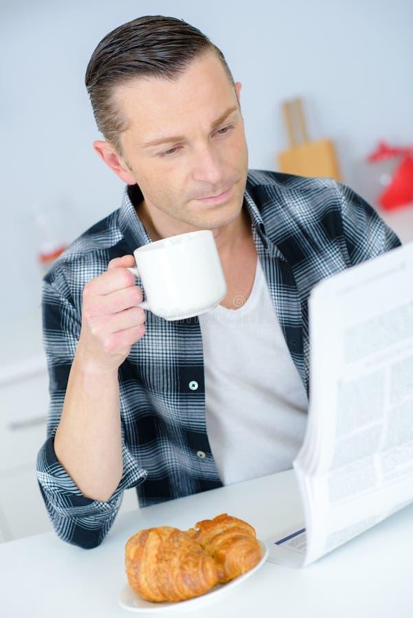 Homme en journal de lecture de chambre d'hôtel avec le petit déjeuner dans le lit photo libre de droits