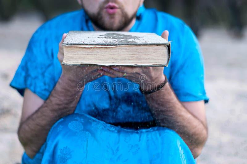 Homme en sable de soufflement de kimono bleu de grand vieux livre image stock