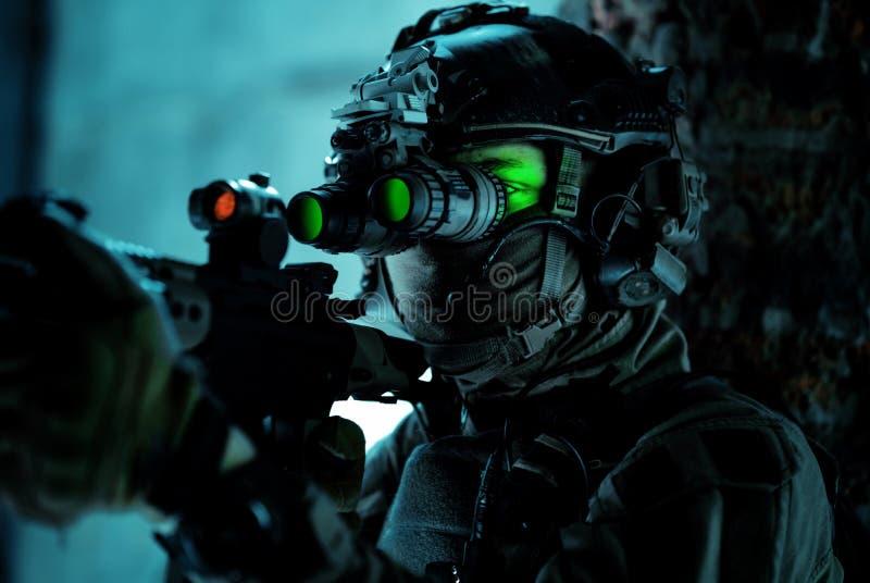 Homme en uniforme avec mitrailleuse et allumé le dispositif de vision nocturne à côté du mur de briques Soldat de l'air de fermet photo libre de droits