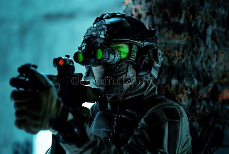 Homme en uniforme avec mitrailleuse et allumé le dispositif de vision nocturne à côté du mur de briques Soldat de l'air de fermet photographie stock libre de droits
