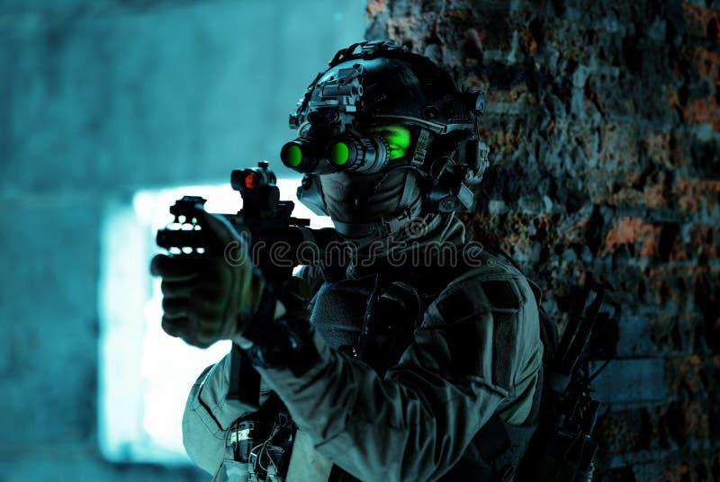 Homme en uniforme avec mitrailleuse et allumé le dispositif de vision nocturne à côté du mur de briques Soldat de l'air de fermet photographie stock