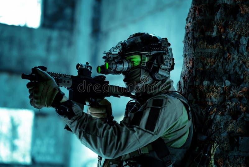 Homme en uniforme avec mitrailleuse et allumé le dispositif de vision nocturne à côté du mur de briques Soldat souple avec feu ve photo stock