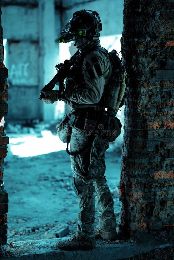 Homme en uniforme avec mitrailleuse et allumé le dispositif de vision nocturne debout entre le mur de briques Soldat de l'air de  photo libre de droits