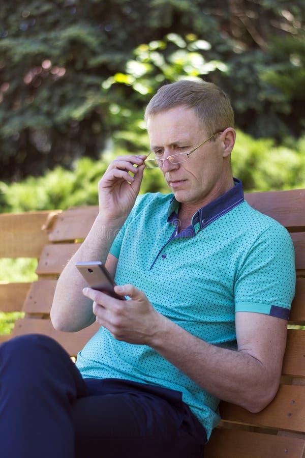 Homme en verres avec le téléphone image libre de droits