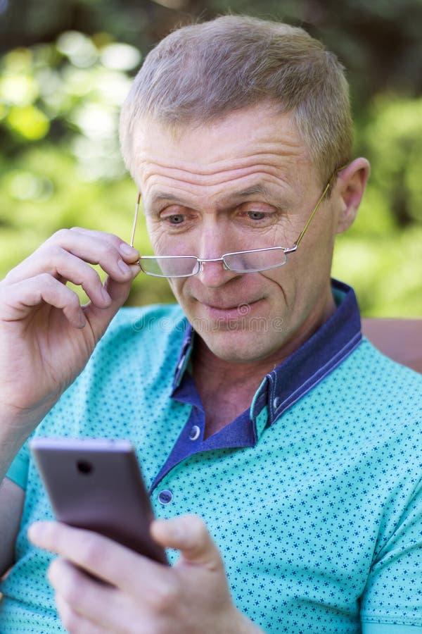 Homme en verres avec le téléphone images libres de droits