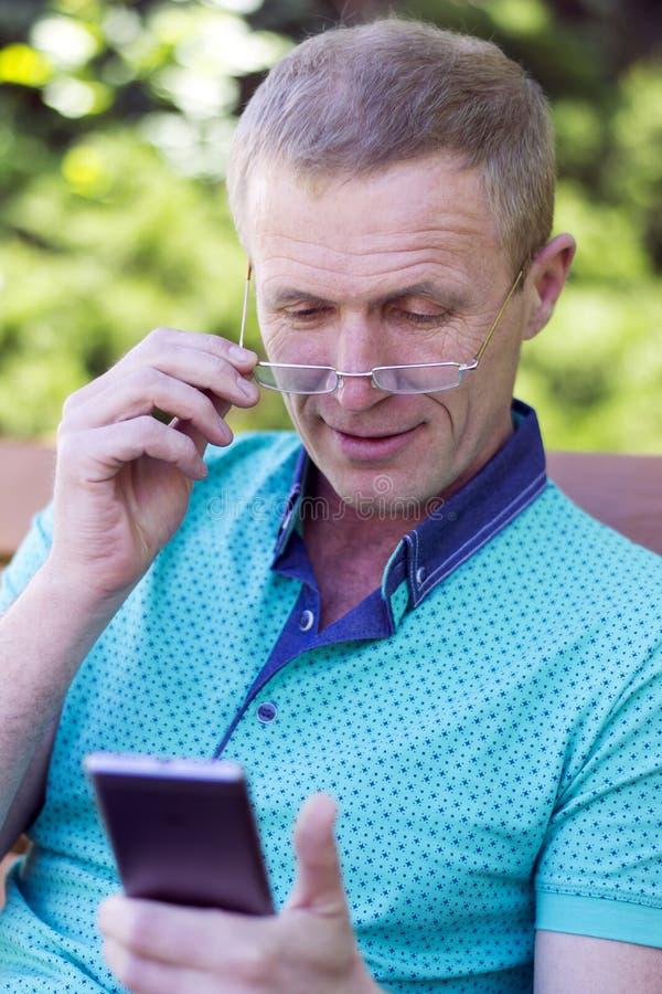 Homme en verres avec le téléphone images stock