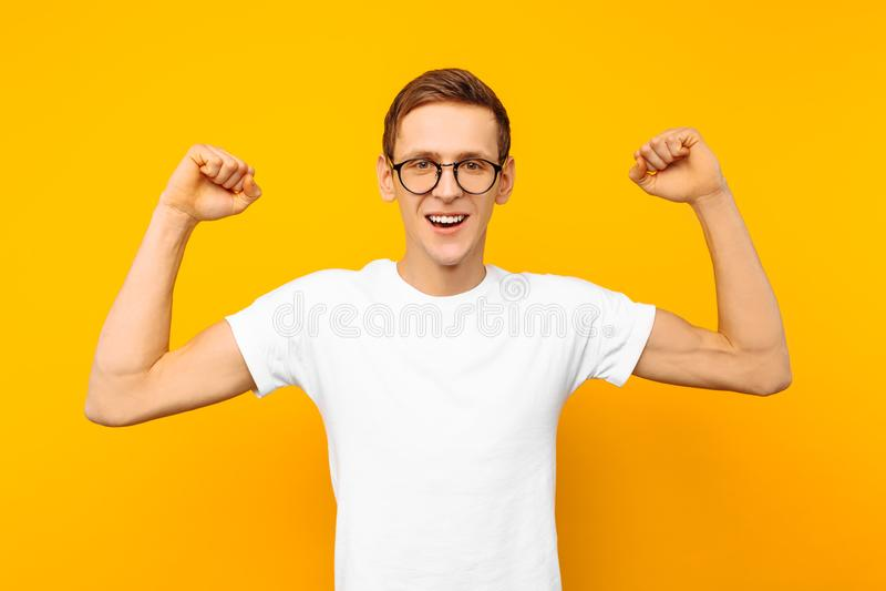 Homme en verres, habillés dans un T-shirt blanc, l'homme qui a gagné des expositions un geste de victoire et de succès, sur un fo photographie stock libre de droits