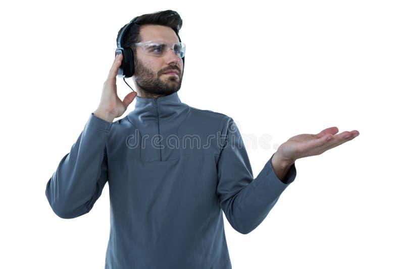 Homme en verres protecteurs faisant des gestes de main tout en écoutant des écouteurs photo stock