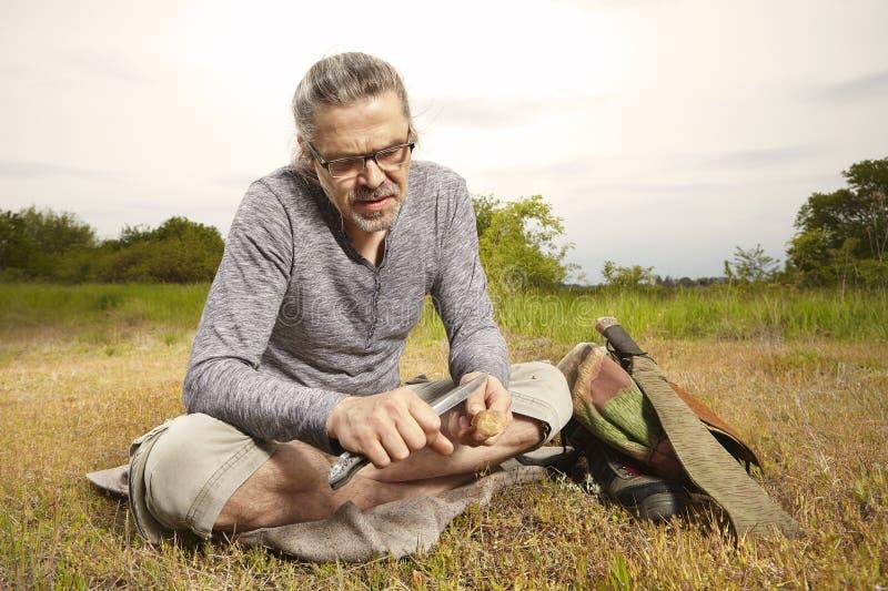 Homme en voyage détendant et découpant la cuillère en nature photographie stock