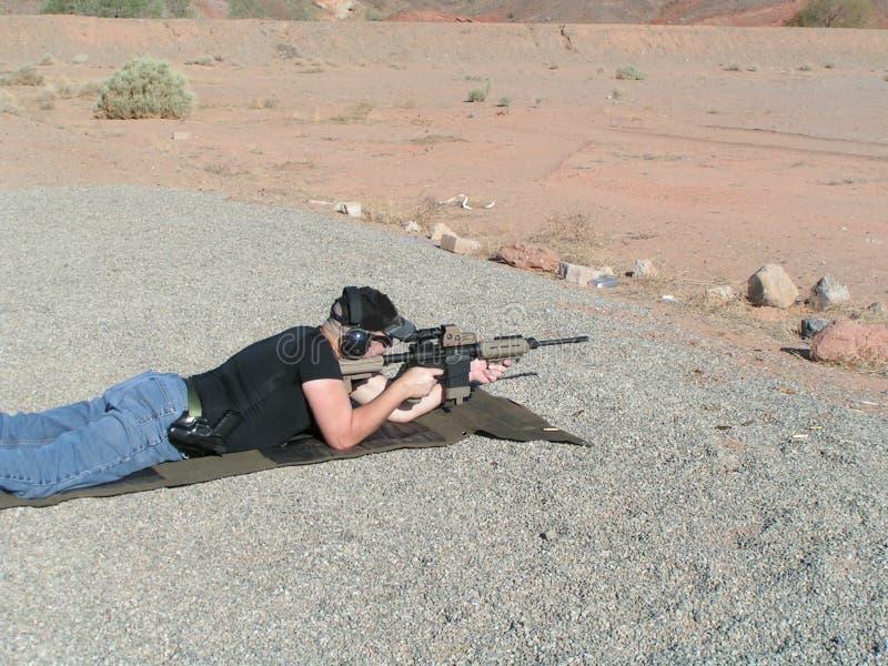 Homme enclin au champ de tir extérieur image stock