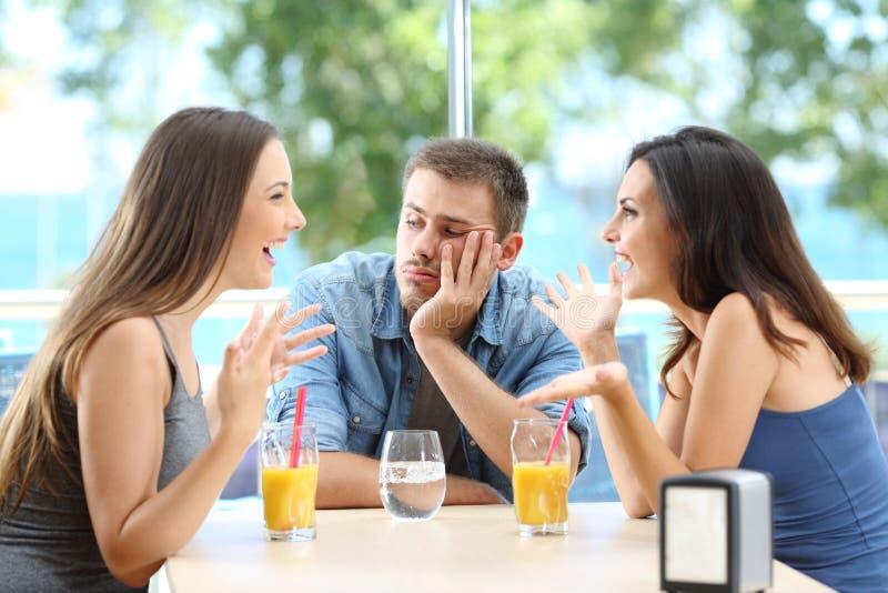 Homme ennuyé écoutant sa conversation d'amis photos stock