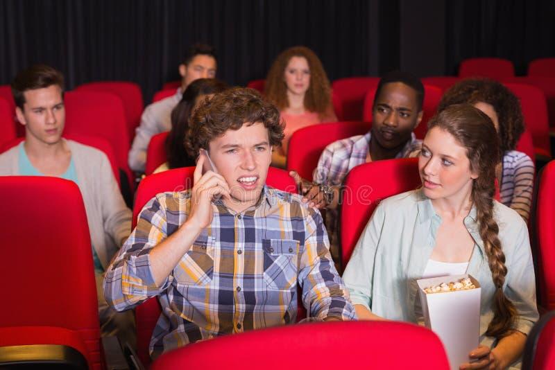 Homme ennuyeux au téléphone pendant le film image libre de droits