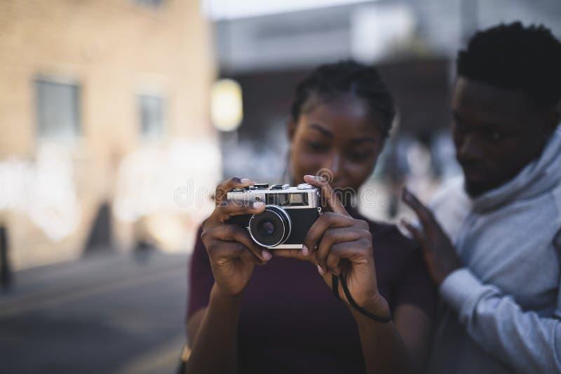 Homme enseignant à son amie comment utiliser une caméra de film de cru images libres de droits