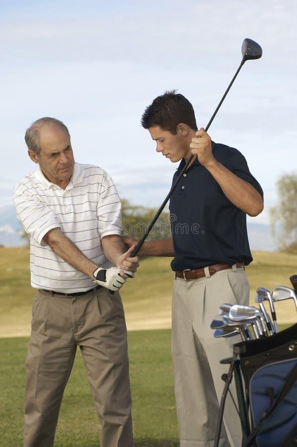 Homme enseignant l'homme supérieur à jouer au golf photo libre de droits