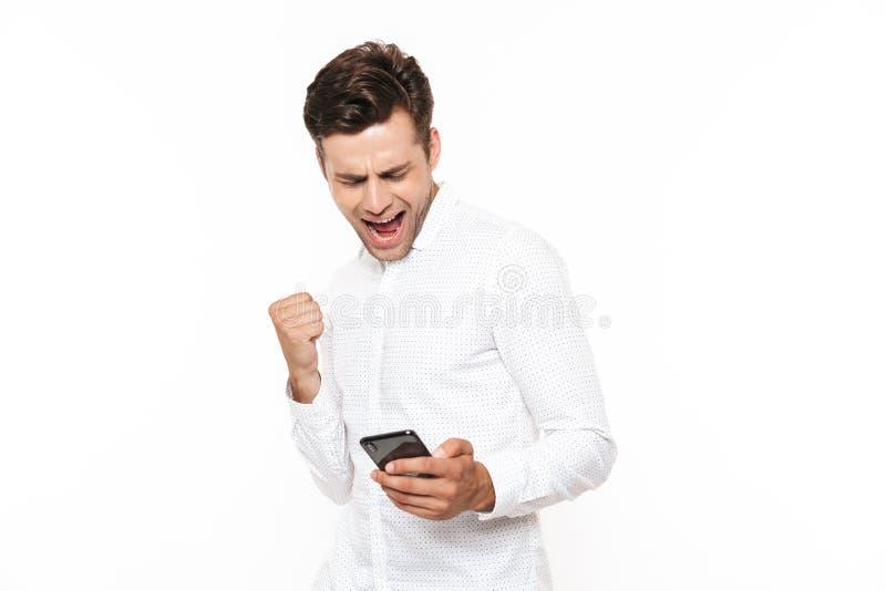 Homme enthousiaste avec les cheveux foncés courts tenant le smartphone et le clenchin images libres de droits