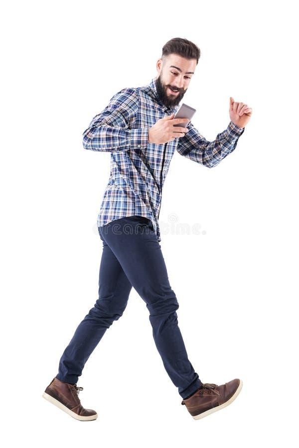 Homme enthousiaste d'affaires regardant sur le téléphone portable fonctionnant dans la hâte Vue de côté photos stock
