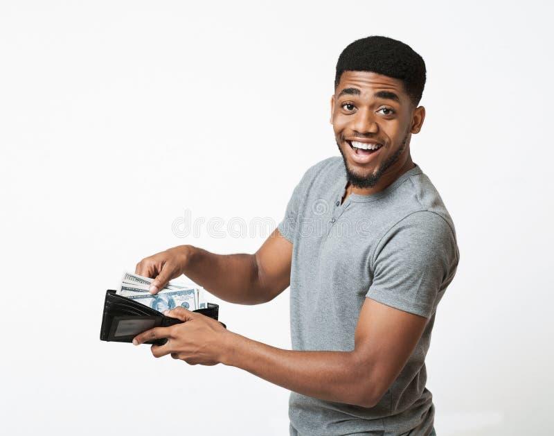 Homme enthousiaste d'afro-américain mettant l'argent dans le portefeuille photographie stock