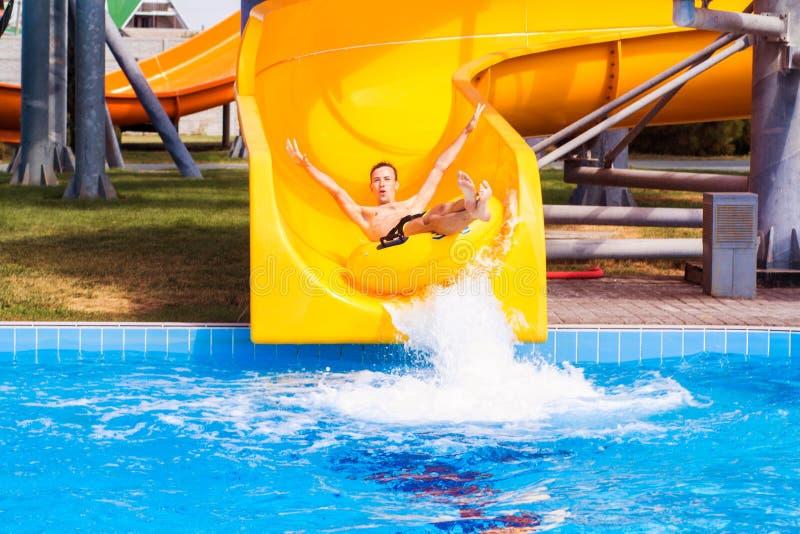 Homme enthousiaste dr?le appr?ciant des vacances d'?t? dans le parc aquatique montant le flotteur jaune photos libres de droits